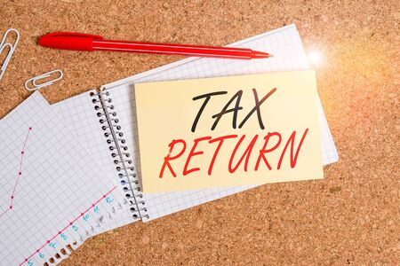 Handwriting text Tax Return. Conceptual photo Tax payer financial information Tax Liability and Payment report Desk notebook paper office cardboard paperboard study supplies table chart