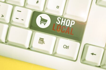 Conceptual hand writing showing Shop Local. Concept meaning a preference to buy locally produced goods and services White pc keyboard with note paper above the white background
