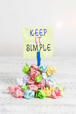 Writing note showing Keep It Simple. Business concept for Easy to toss around Understandable Generic terminology Reminder pile colored crumpled paper clothespin wooden space