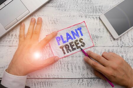 Word writing text Plant Trees. Business photo showcasing process of planting a tree for land cultivation and forestry Hand hold note paper near writing equipment and modern smartphone device