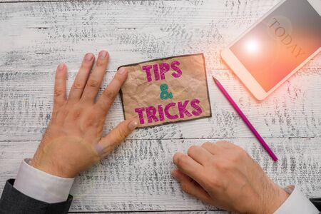 Text sign showing Tips And Tricks. Business photo text Steps Lifehacks Handy advice Recommendations Skills Hand hold note paper near writing equipment and modern smartphone device