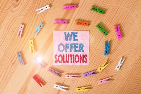 Conceptual hand writing showing We Offer Solutions. Concept meaning Offering help assistance Experts advice strategies ideas Colored crumpled papers wooden floor background clothespin