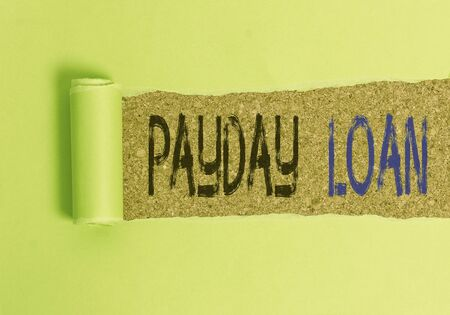 Text sign showing Payday Loan. Business photo text Something lent or furnished on condition being returned Cardboard which is torn in the middle placed above a wooden classic table