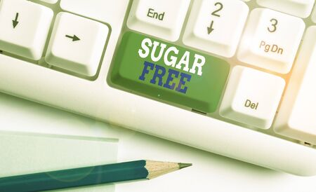 Text sign showing Sugar Free. Business photo text containing an artificial sweetening substance instead of sugar White pc keyboard with empty note paper above white background key copy space Zdjęcie Seryjne - 134314949