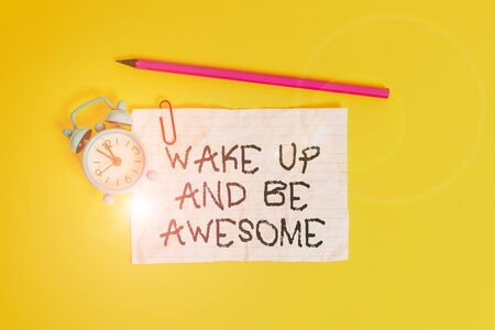 Conceptual hand writing showing Wake Up And Be Awesome. Concept meaning Rise up and Shine Start the day Right and Bright Metal alarm clock ccrushed sheet pencil colored background