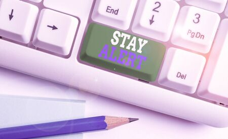 Text sign showing Stay Alert. Business photo text Paying full attention to things around Quick to see or understand White pc keyboard with empty note paper above white background key copy space