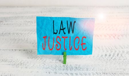 Word writing text Law Justice. Business photo showcasing a scheme or system of law in which every demonstrating receives Green clothespin white wood background colored paper reminder office supply