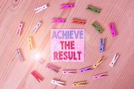 Conceptual hand writing showing Achieve The Result. Concept meaning Receive successful result from hard work make you happy Colored crumpled papers wooden floor background clothespin