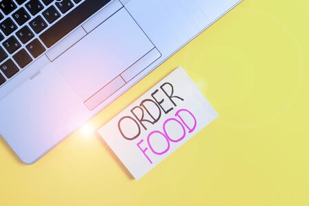 Word writing text Order Food. Business photo showcasing the process of requesting a preferred food in a restaurant Slim trendy silver open laptop square sticky notepad colored background