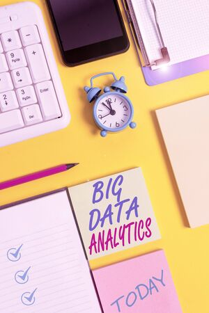 Writing note showing Big Data Analytics. Business concept for The process of examining large and varied data sets White paper with copy space with paper clips clock and pc keyboard