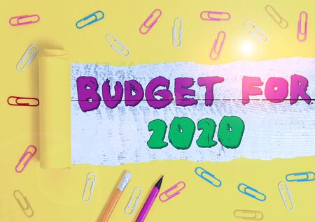Word writing text Budget For 2020. Business photo showcasing An written estimates of income and expenditure for 2020 Stationary and torn cardboard placed above a wooden classic table backdrop Archivio Fotografico