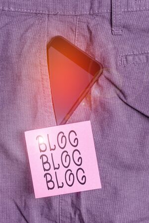Handwriting text Blog Blog Blog. Conceptual photo Internet blogging trend modern virtual communication Smartphone device inside formal work trousers front pocket near note paper