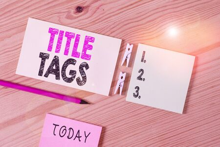 Conceptual hand writing showing Title Tags. Concept meaning the HTML element that specifies the title of a web page Colored crumpled papers wooden floor background clothespin