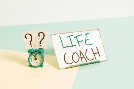 Handwriting text Life Coach. Conceptual photo someone who helps identify your goals and plan to achieve them Mini size alarm clock beside a Paper sheet placed tilted on pastel backdrop