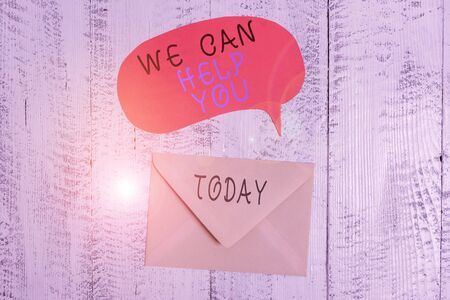 Handwriting text writing We Can Help You. Conceptual photo Support Assistance Offering Customer Service Attention Front view closed envelop speech bubble lying wooden vintage background