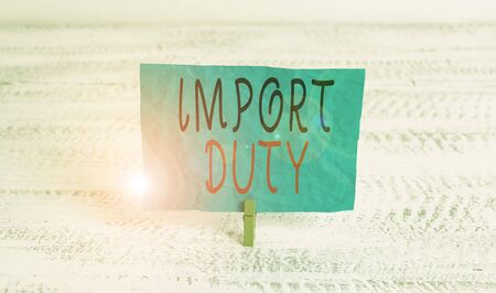 Word writing text Import Duty. Business photo showcasing tax imposed by a government on goods from other countries Green clothespin white wood background colored paper reminder office supply Zdjęcie Seryjne