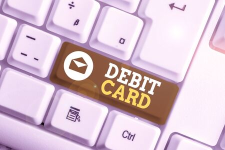 Conceptual hand writing showing Debit Card. Concept meaning card that deducts money directly from a demonstrating s is checking account White pc keyboard with note paper above the white background