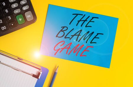 Writing note showing The Blame Game. Business concept for A situation when showing attempt to blame one another Clipboard blank sheet square page calculator pencil colored background