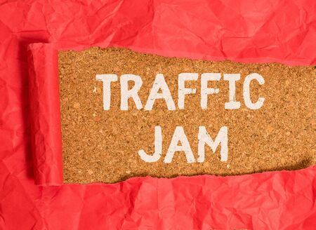 Handwriting text Traffic Jam. Conceptual photo a large number of vehicles close together and unable to move Cardboard which is torn in the middle placed above a wooden classic table