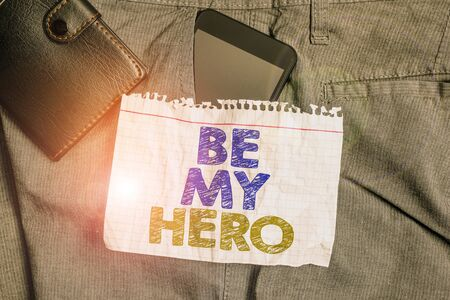Word writing text Be My Hero. Business photo showcasing Request by someone to get some efforts of heroic actions for him Smartphone device inside trousers front pocket with wallet and note paper Imagens