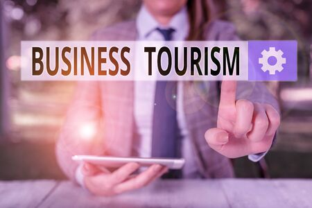 Conceptual hand writing showing Business Tourism. Concept meaning activity of leaving one s is native place for business purpose Female business person sitting by table holding mobile phone