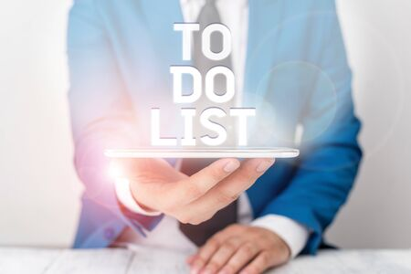 Text sign showing To Do List. Business photo text A structure that usualy made in paper contining task of yours Businessman in blue suite with a tie holds lap top in hands Stock fotó