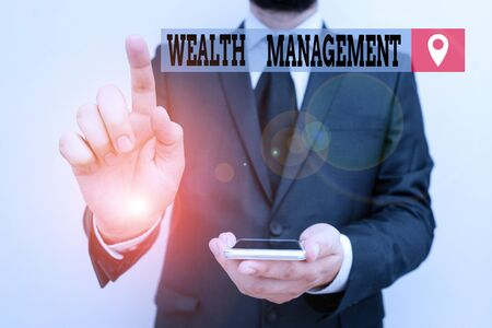 Writing note showing Wealth Management. Business concept for perforanalysisce tracking of the funds as per regular market Male human wear formal work suit hold smartphone using hand Stock Photo