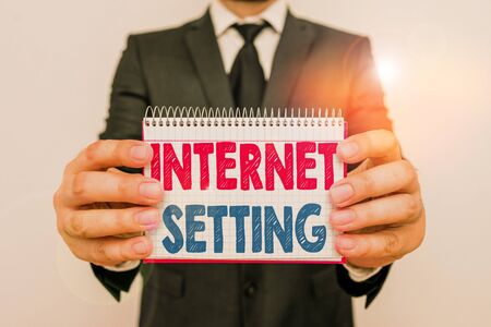 Writing note showing Internet Setting. Business concept for etermines how it connects to your wireless carrier for data Male human wear formal work suit with office look hold book