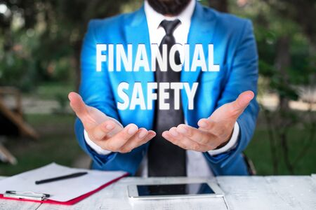 Text sign showing Financial Safety. Business photo showcasing enough money saved to cover emergencies and financial goals Man with opened hands in fron of the table. Mobile phone and notes on the table