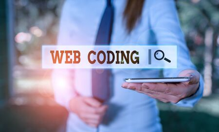 Writing note showing Web Coding. Business concept for work involved in developing a web site for the Internet Business woman in shirt holding laptop and mobile phone Stock Photo