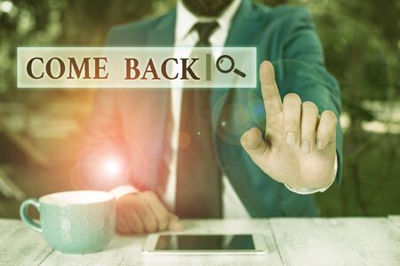 Conceptual hand writing showing Come Back. Concept meaning asking for a demonstrating to return place where love ones resides Businessman with pointing finger in front of him Stock Photo