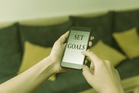 Word writing text Set Goals. Business photo showcasing Defining or achieving something in the future based on plan woman using smartphone office supplies technological devices inside home