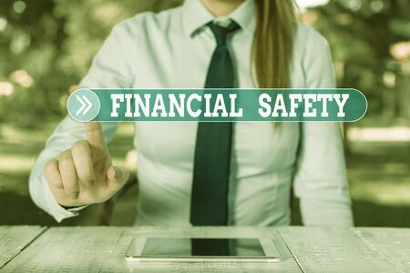 Word writing text Financial Safety. Business photo showcasing enough money saved to cover emergencies and financial goals Female business person sitting by table and holding mobile phone