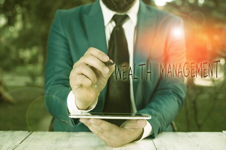 Writing note showing Wealth Management. Business concept for perforanalysisce tracking of the funds as per regular market Businessman pointing with pen in empty copy space Stock Photo