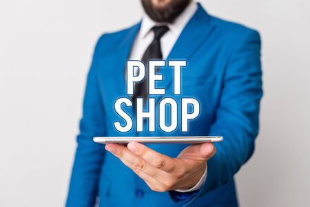 Conceptual hand writing showing Pet Shop. Concept meaning Retail business that sells different kinds of animals to the public Businessman in blue suite with a tie holds lap top in hands