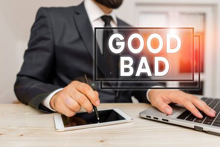 Writing note showing Good Bad. Business concept for to seem to be going to have a good or bad result Life choices Male human wear formal clothes present use hitech smartphone