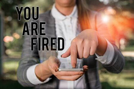 Word writing text You Are Fired. Business photo showcasing Getting out from the job and become jobless not end the career Woman in grey suites holds mobile phone
