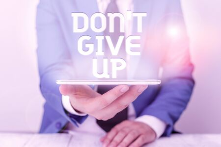 Text sign showing Don T Give Up. Business photo text Determined Persevering Continue to Believe in Yourself Businessman in blue suite with a tie holds lap top in hands