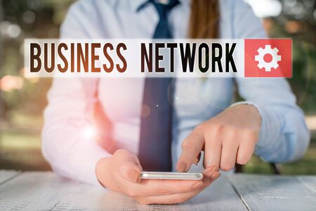 Conceptual hand writing showing Business Network. Concept meaning Interfirm cooperation that allows companies to collaborate Female business person sitting and holding mobile phone