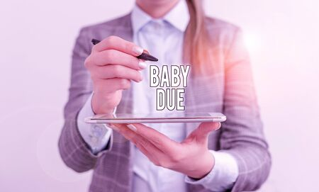Handwriting text Baby Due. Conceptual photo about to born Under engagement as to time Expected to be ready Business concept with mobile phone and business woman Standard-Bild - 134495834