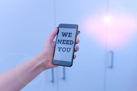Writing note showing We Need You. Business concept for Company wants to hire Vacancy Looking for talents Job employment woman using smartphone and technological devices inside the home