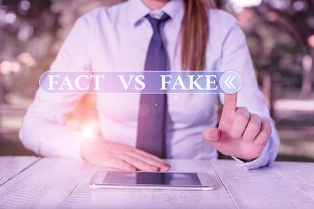Handwriting text Fact Vs Fake. Conceptual photo Rivalry or products or information originaly made or imitation Female business person sitting by table and holding mobile phone Stock Photo