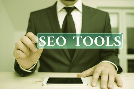 Conceptual hand writing showing Seo Tools. Concept meaning process of affecting online visibility of website or page Male human wear formal clothes present use hitech smartphone
