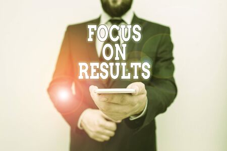 Text sign showing Focus On Results. Business photo showcasing concentrating on certain actions gains and goals Male human wear formal work suit hold smart hi tech smartphone use one hand