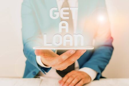 Text sign showing Get A Loan. Business photo text mount of money that is borrowed often from bank has paid back Businessman in blue suite with a tie holds lap top in hands Фото со стока