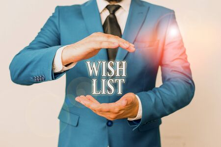 Conceptual hand writing showing Wish List. Concept meaning List of desired but often realistically unobtainable items Man in front of table. Mobile phone and notes on the table