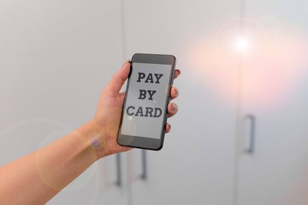Writing note showing Pay By Card. Business concept for Payments on credit Debit Electronic Virtual Money Shopping woman using smartphone and technological devices inside the home