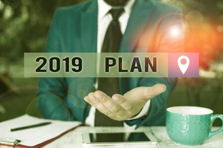 Writing note showing 2019 Plan. Business concept for Challenging Ideas Goals for New Year Motivation to Start Man in front of table. Mobile phone and notes on the table