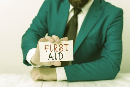 Word writing text First Aid. Business photo showcasing Practise of healing small cuts that no need for medical training Man holds empty paper with copy space in front of him Space Reklamní fotografie