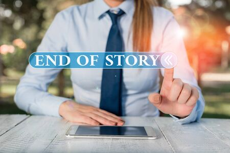 Handwriting text End Of Story. Conceptual photo Emphasize that nothing to add Literature writing Journalism Female business person sitting by table and holding mobile phone